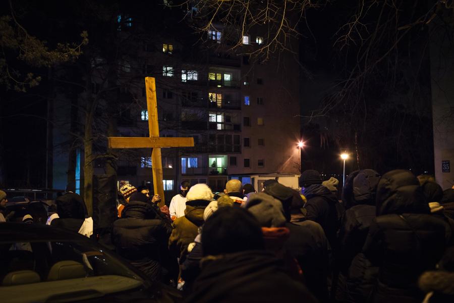 Droga Krzyżowa ulicami dzielnicy - stacja pomiędzy blokami. Niektórzy patrzą przezokna. Inni zajęci swoimi sprawami.
